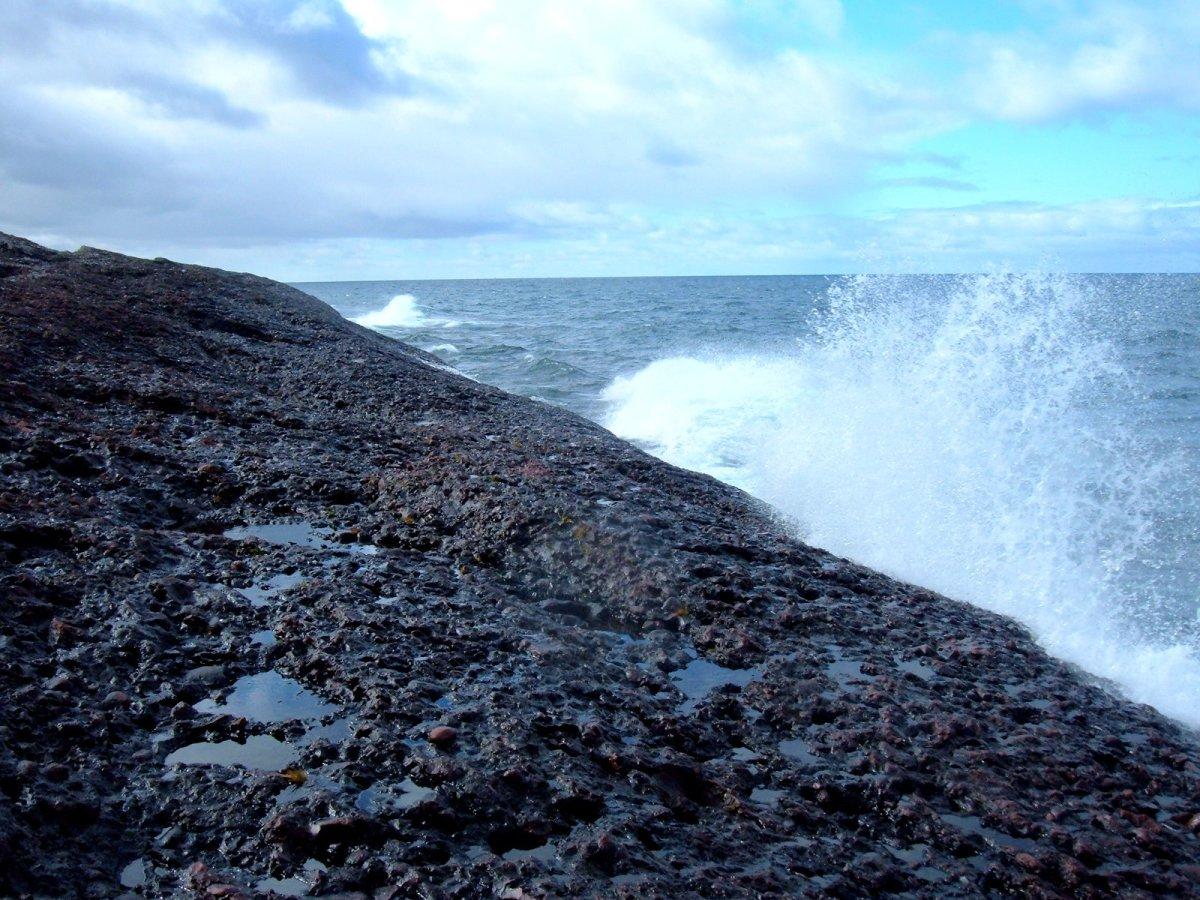 Waves of Lake Superior break on the solid rock beach at Horseshoe Bay on Michigan's Keweenaw Peninsula.