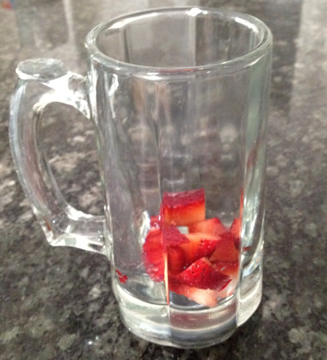 1. Fill bottom of clear glass or mug with diced strawberries.