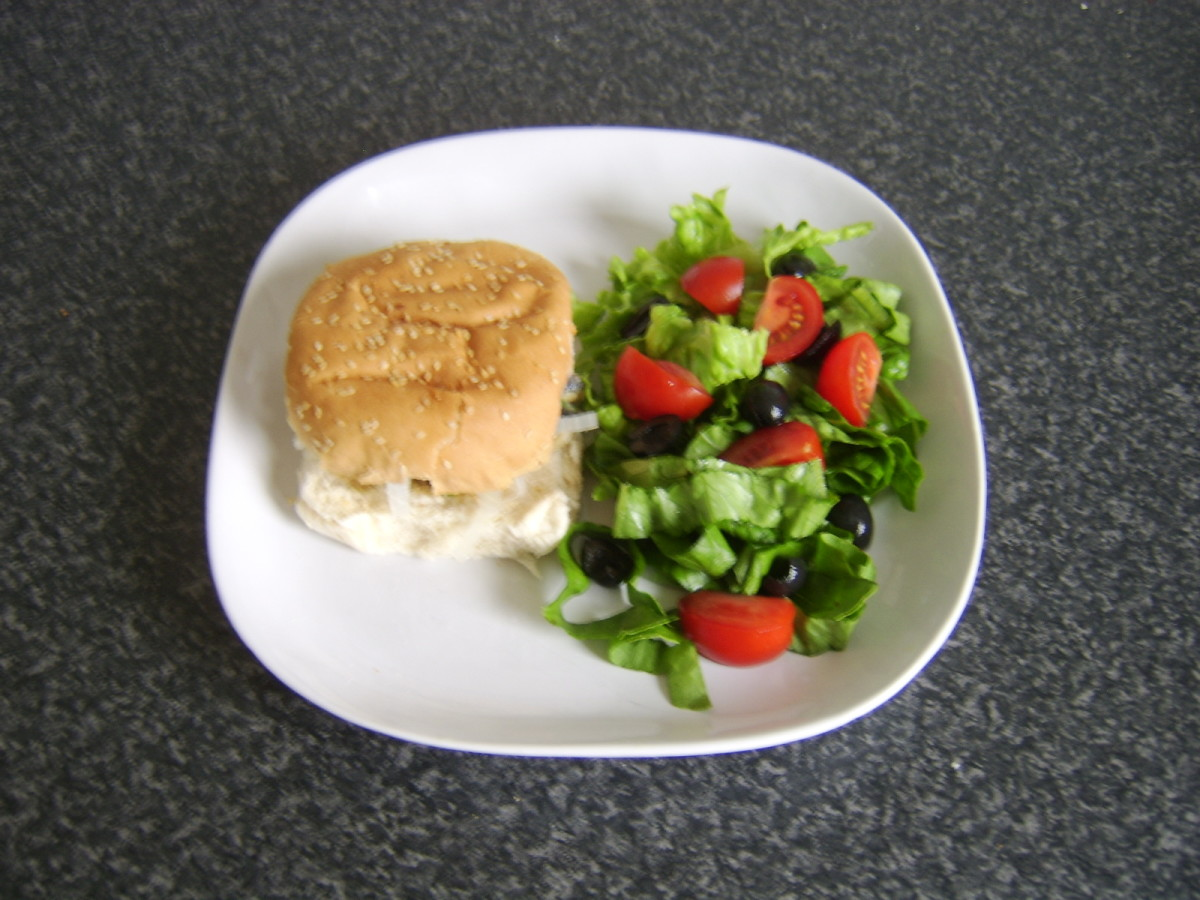 Rollmop on herb buttered burger bun with salad is ready to serve