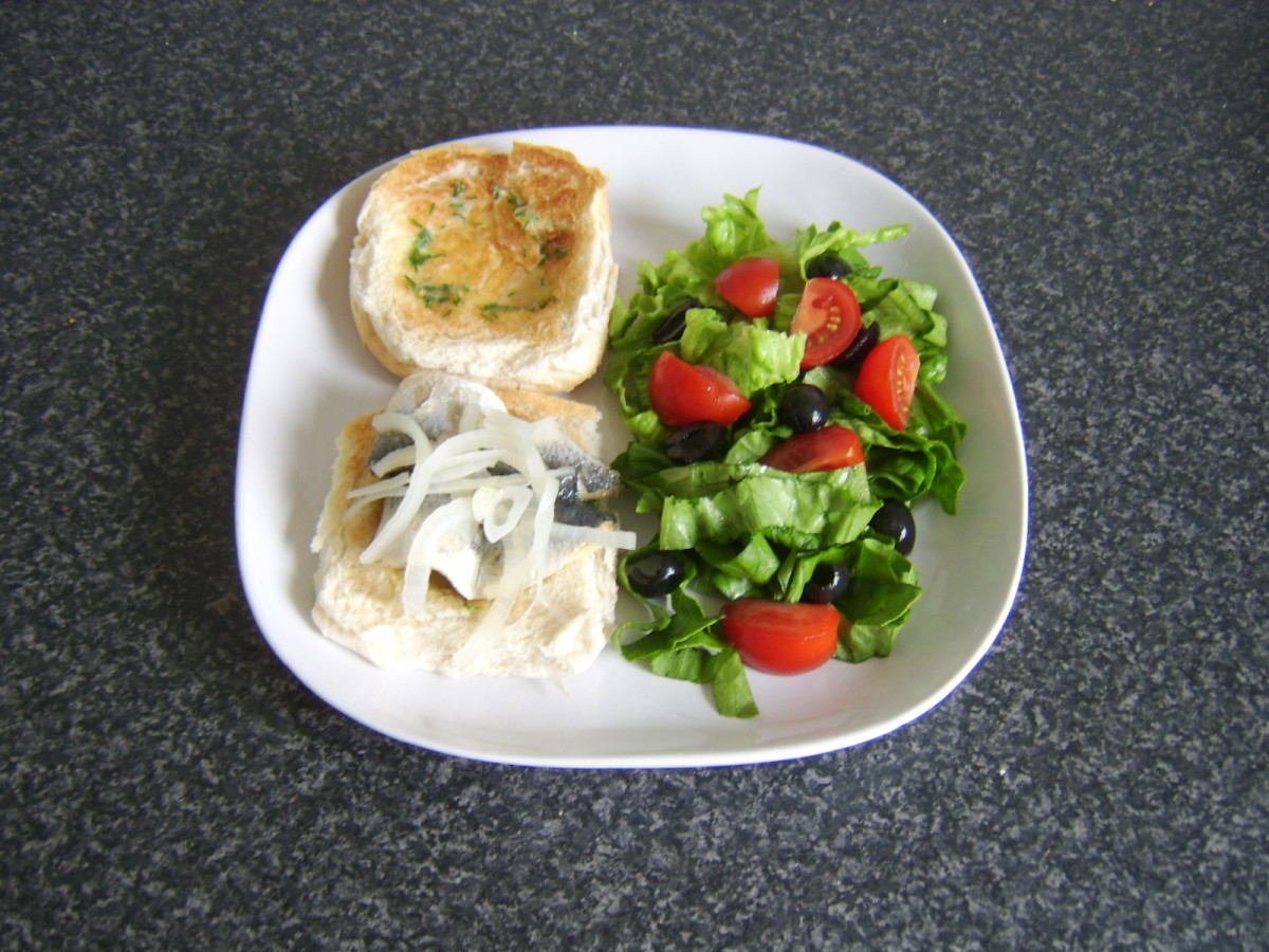A pickled herring fillet on a herb buttered burger bun with salad makes a fairly unorthodox but delicious meal!