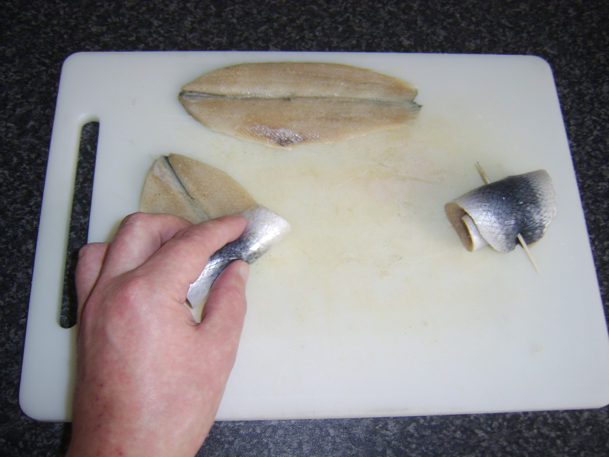 Herring fillets are rolled and skewered with wooden cocktail sticks