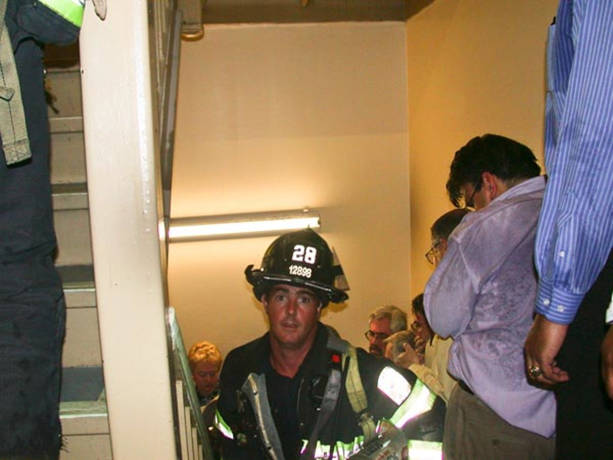 Fireman Mike Kehoe heads upstairs while others flee downstairs. Kehoe luckily survived the building collapses.