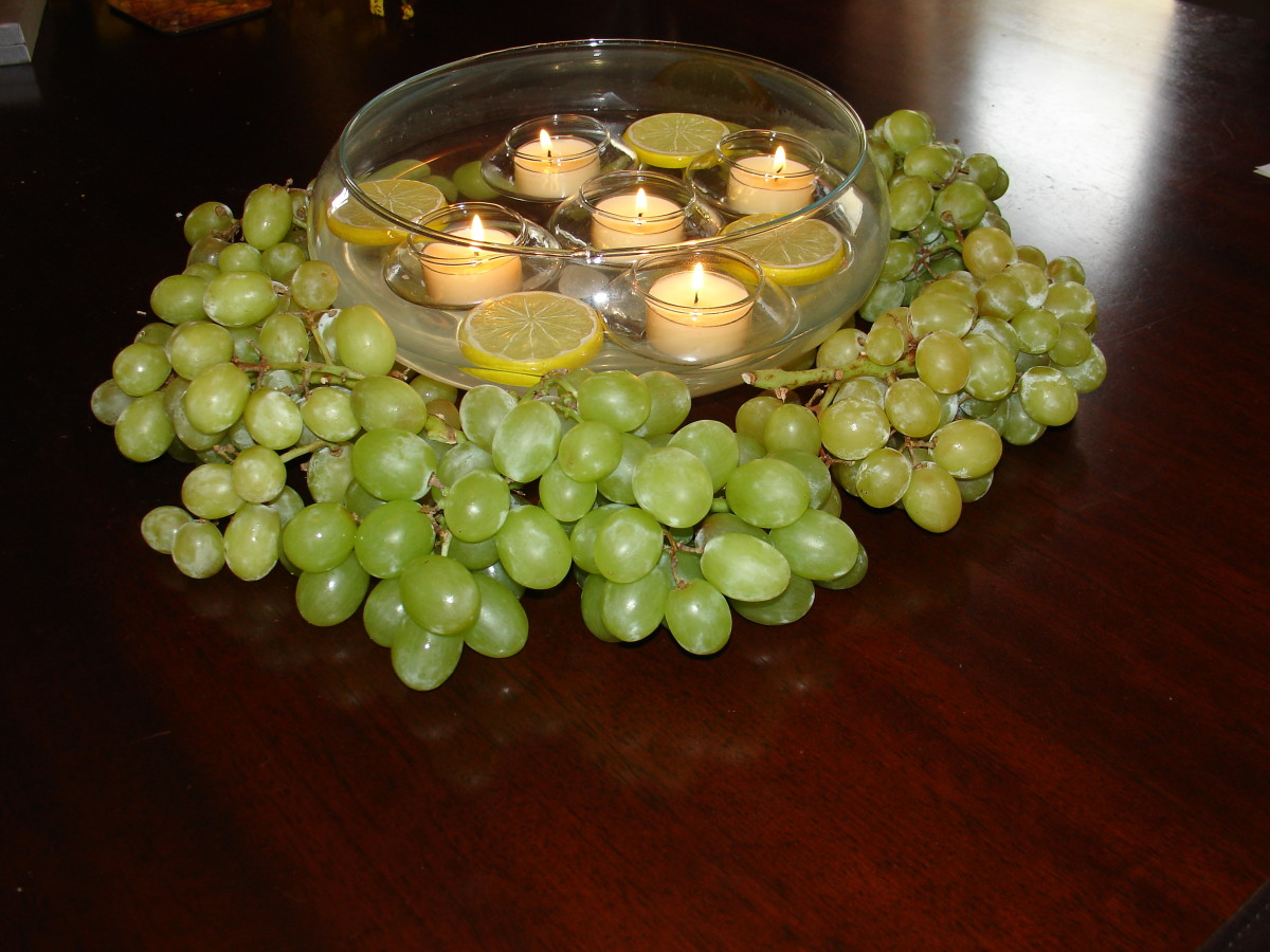 A very simple centerpiece, floating candles among lemon slices, surrounded by grapes.
