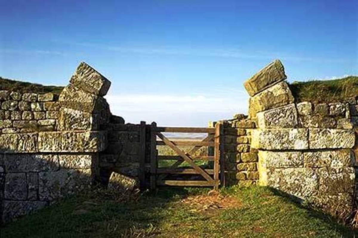 Milecastle gateway with the wall base and part of the arch put into use with a slightly more modern wooden gate