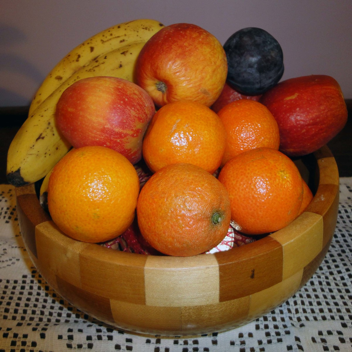 Chequered light and dark solid wood with banana, oranges, apples and plums