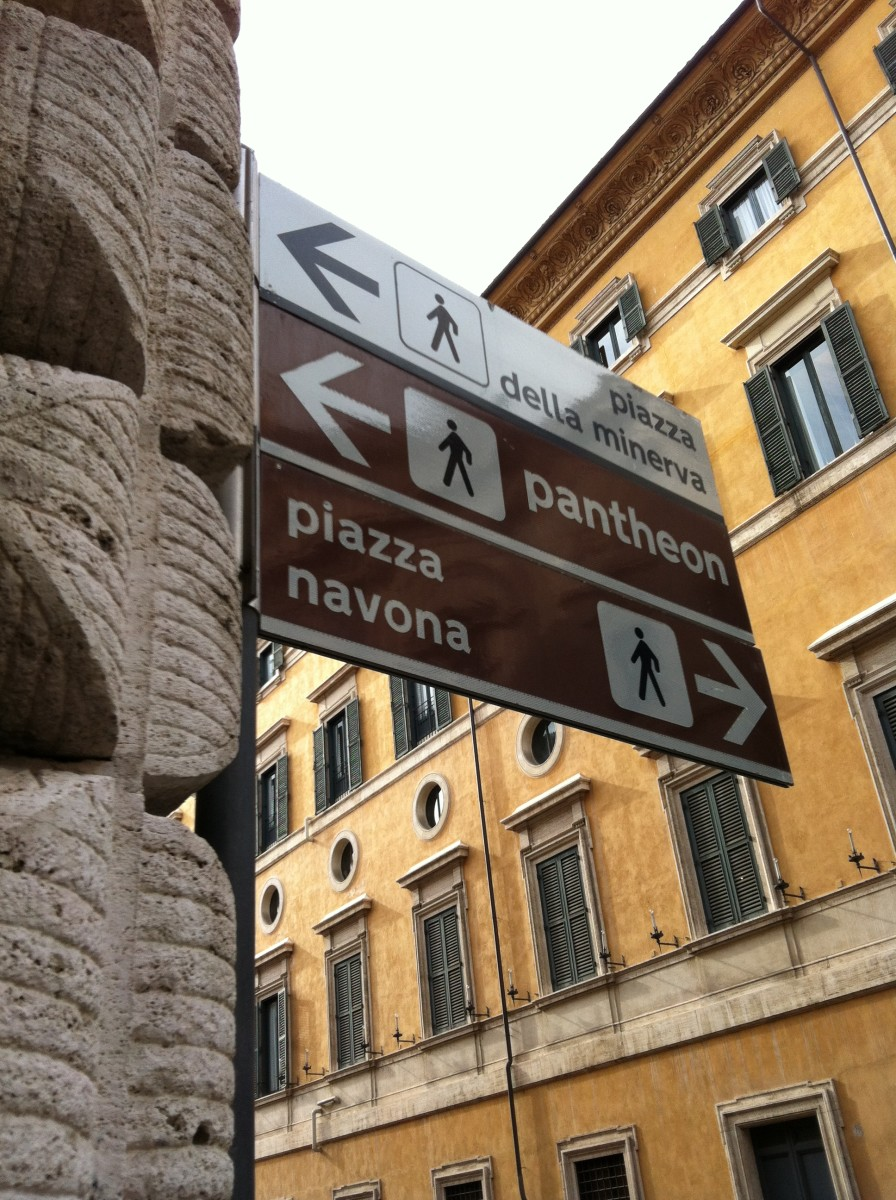Street sign outside the church of San Luigi for Piazza Navona and the Pantheon which are within 100 meters