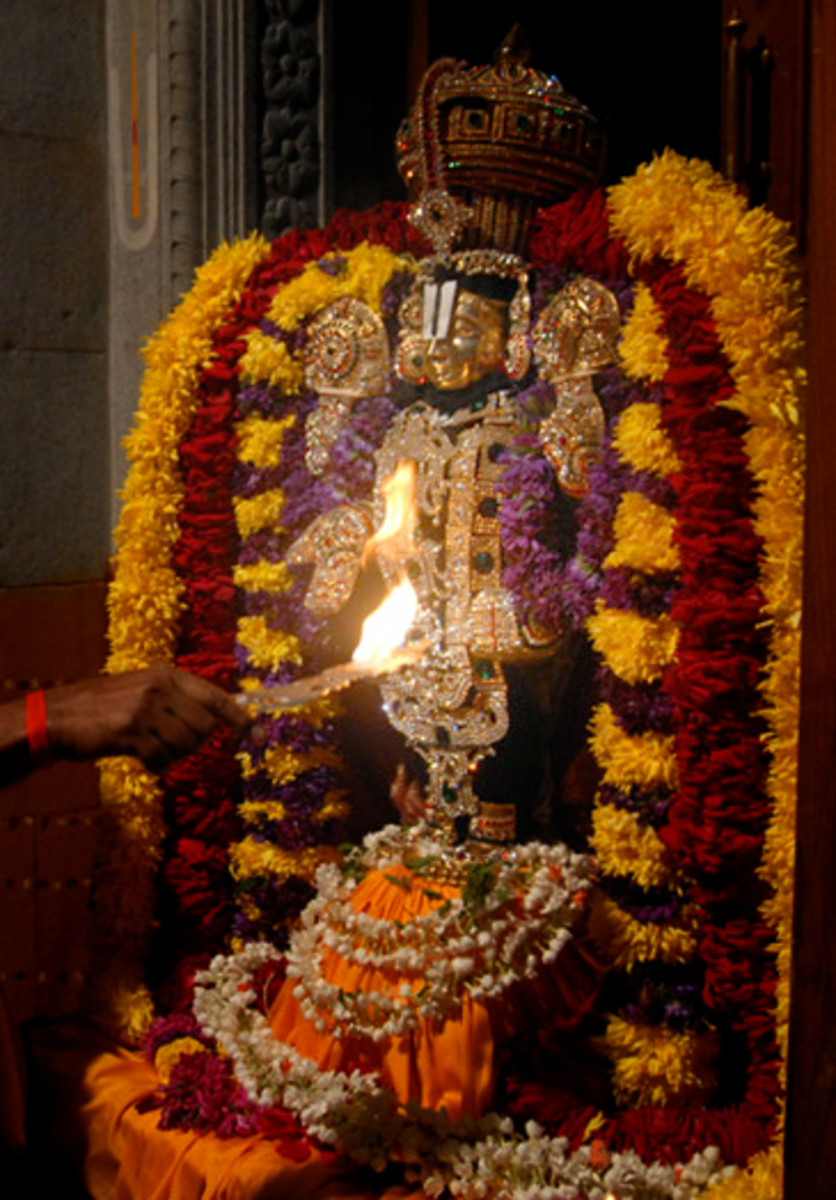 The flame lights up the the beautifully bedecked idol for all the devotees to see and experience joy.