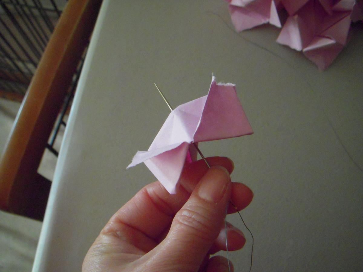 Thread paper flower onto needle, through center of flower.
