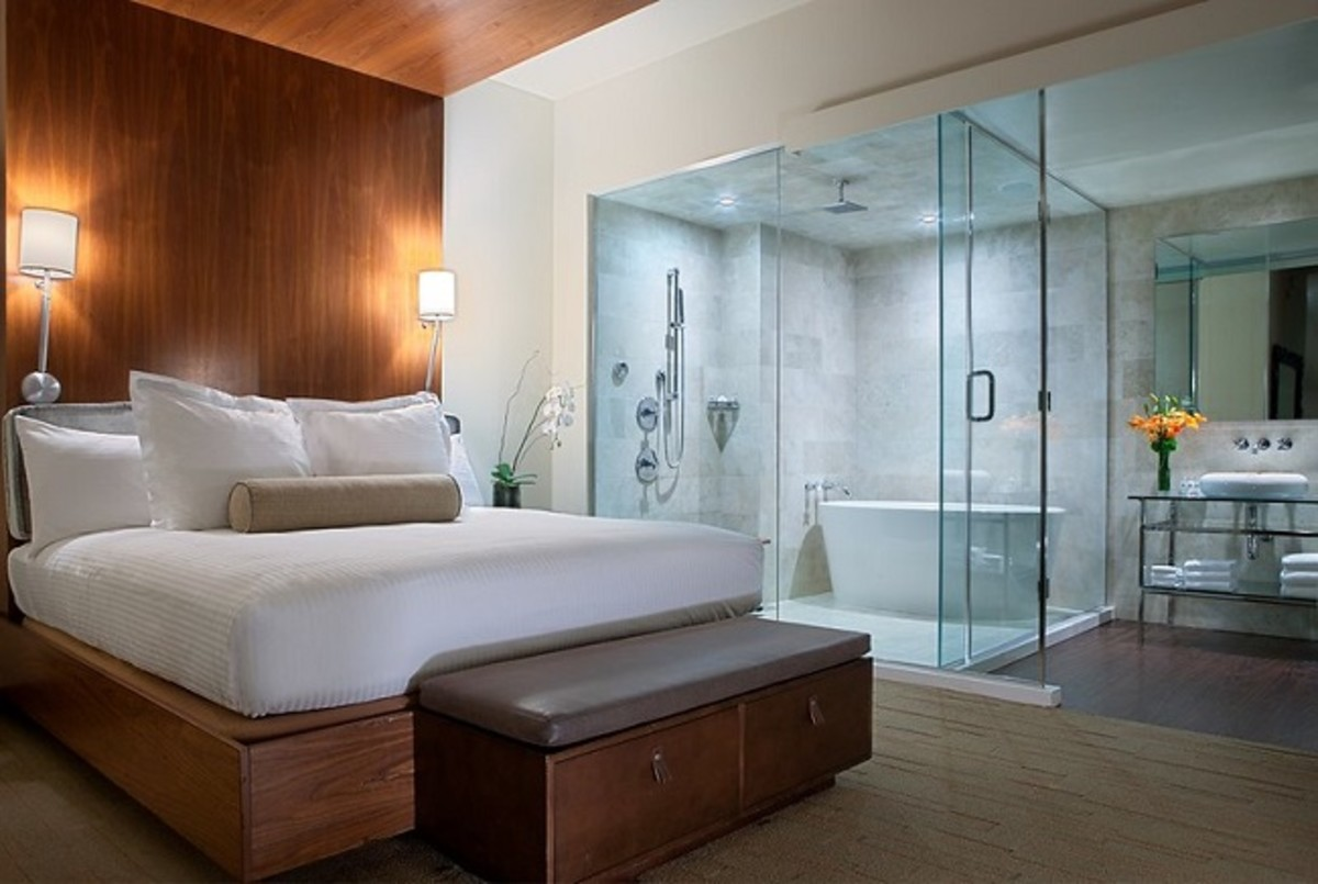 Modern bedroom suite with minimal furnishings and clean-line furniture. A modern elegant bathroom can be viewed from the bedroom area..