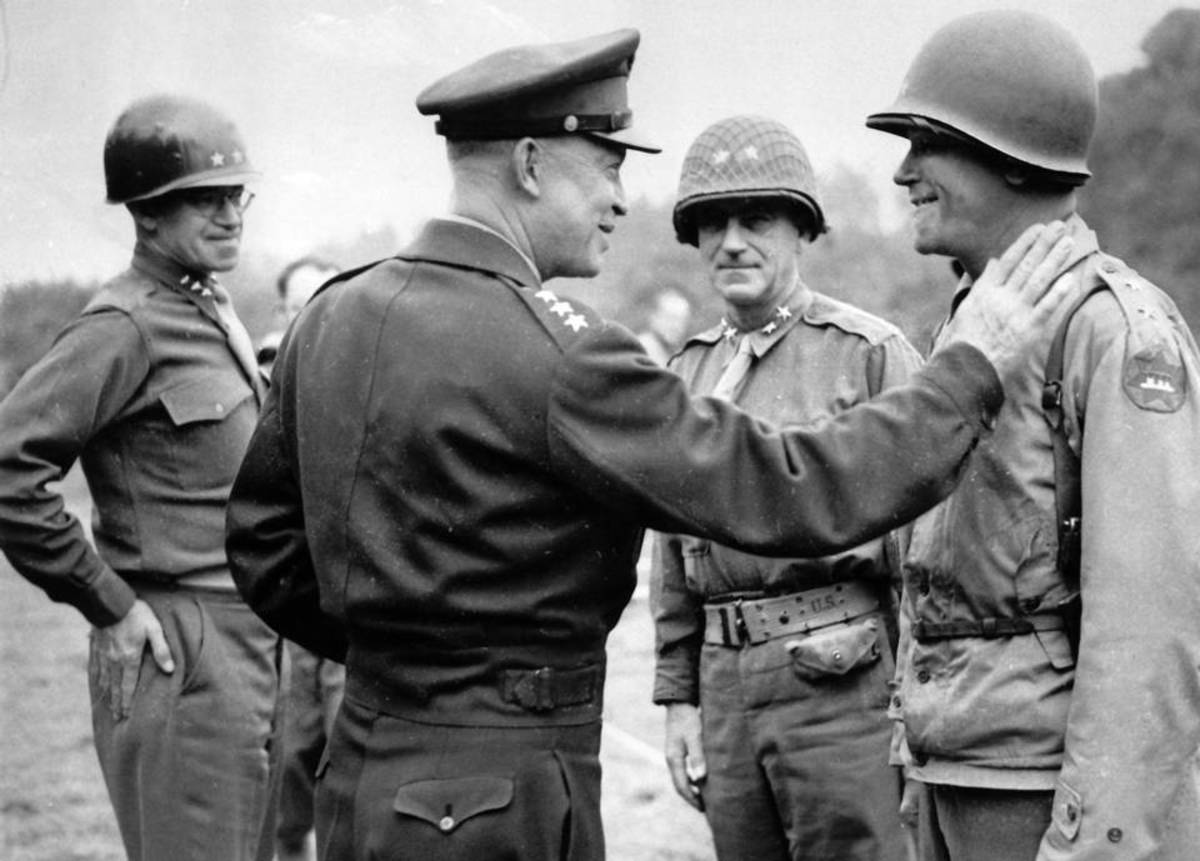 Eisenhower jokes with General Collins as Bradley and Gerow look on.
