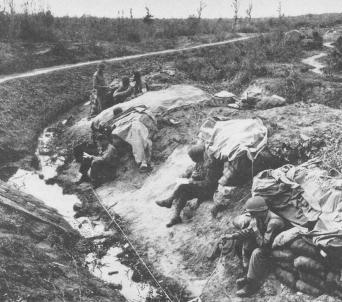 Hurry Up and Wait: GIs outside their bunkers near Anzio beach.