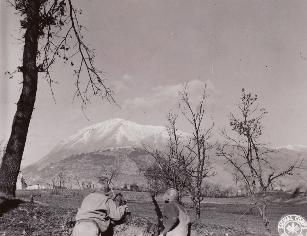 Two GIs in the Rapido Valley look out upon The Abbey at Monte Cassino. Brutal terrain caused excessive delays and created great defensive positions for the Germans.