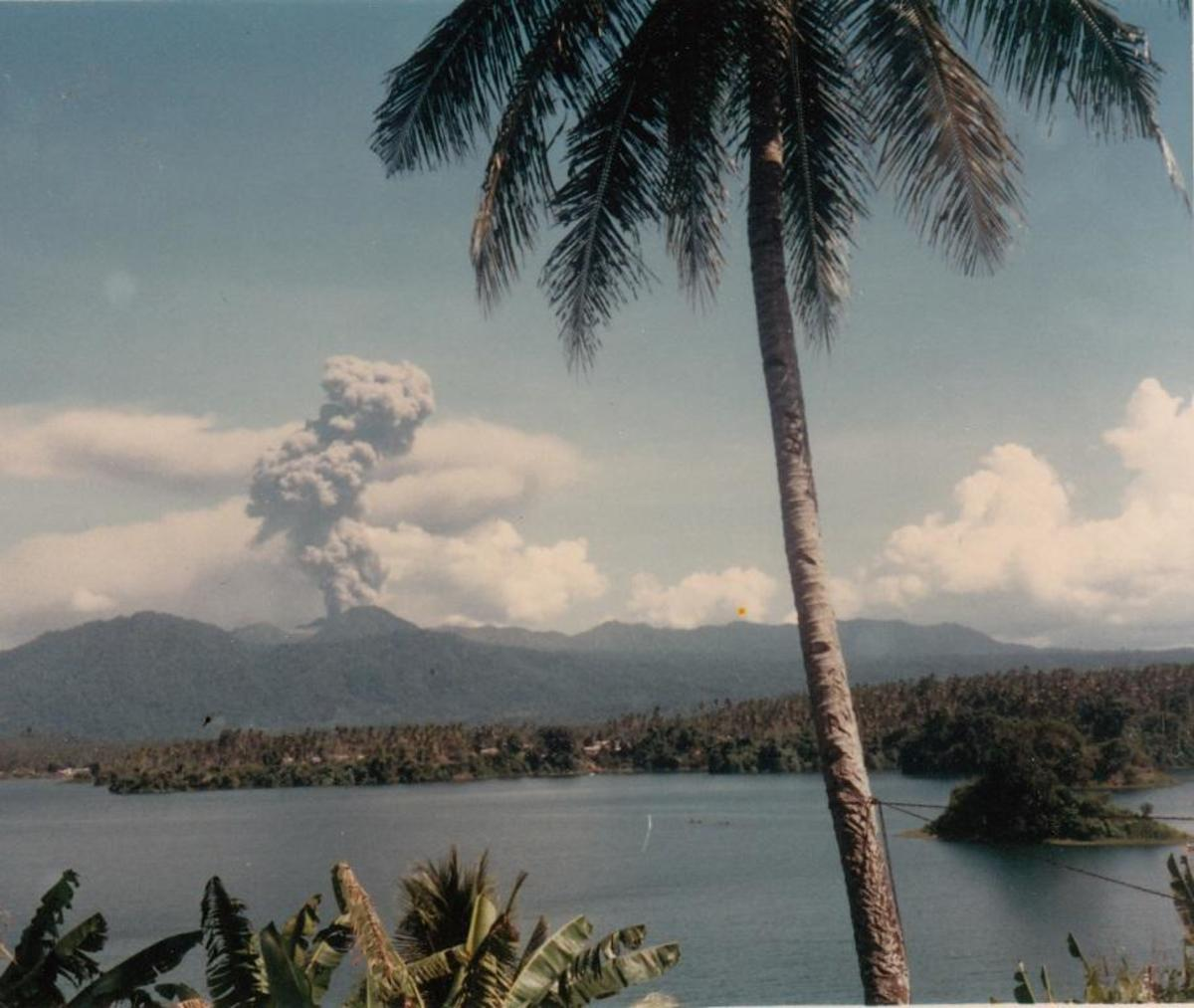 View of island in the lake and active volcano in the distance.