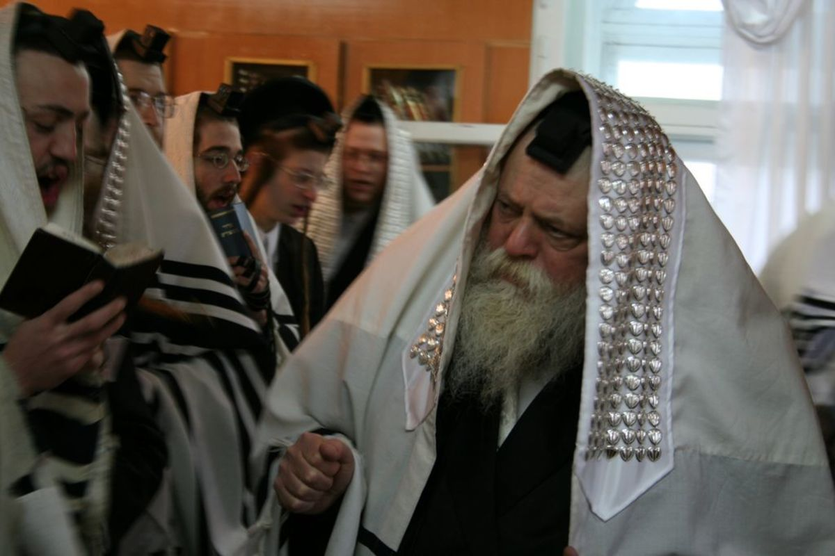 Orthodox Rabbi and worshippers during morning prayers, in prayer shawls and with prayer books