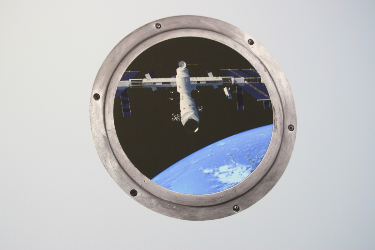 """A space """"porthole"""" wall decal ordered from Etsy. This decal cost approximately $13 and adds punch to the room."""