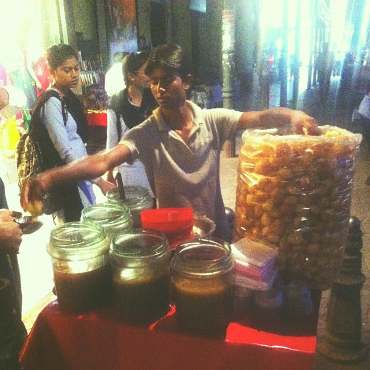 A vendor with the round puris and the different flavored water in different containers in front of him