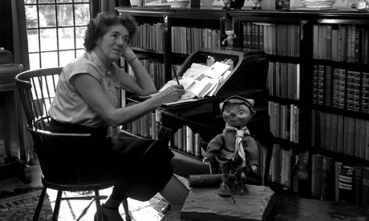 Enid Blyton answering letters from children with a Noddy statue by her side