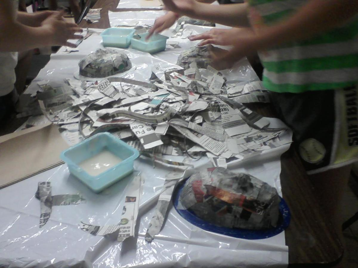 Newspaper is torn into strips, then dipped into the paper mache paste and layered onto the mold
