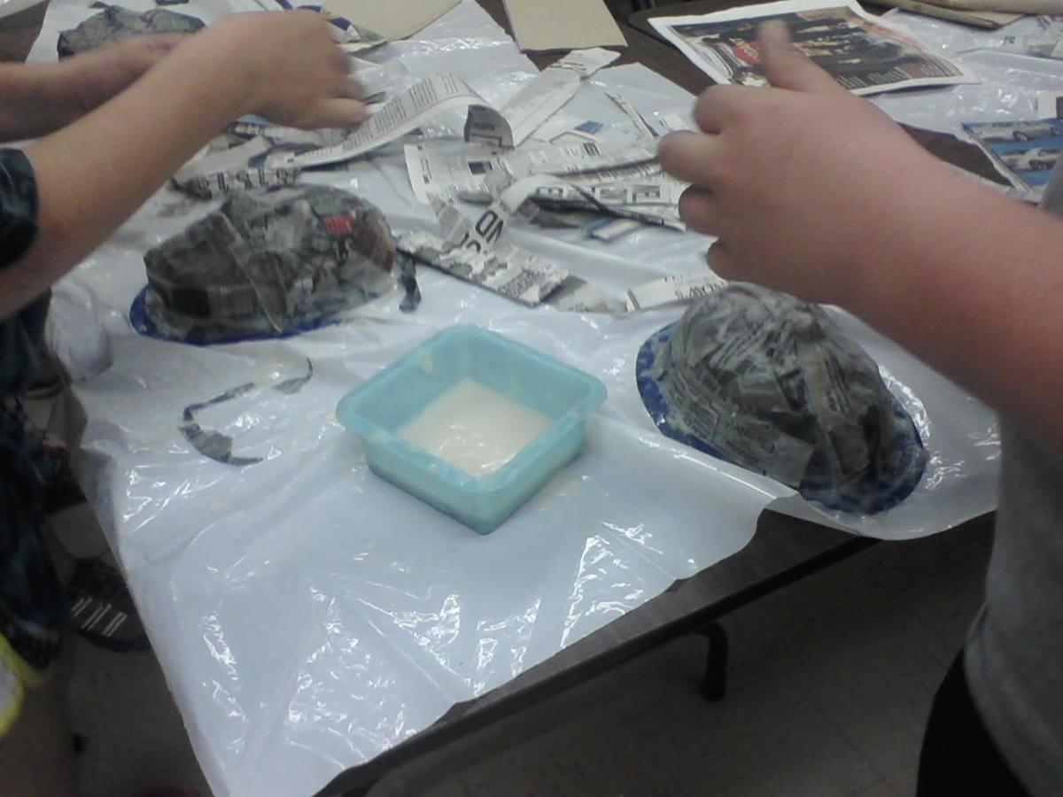 The students should use at least three layers of paper mache to make the masks sturdy, the more layers of paper, the stronger the mask