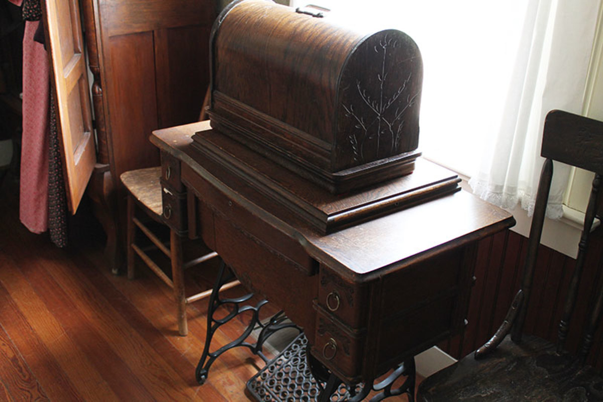 This is a vintage treadle machine with another machine and case on top. Probably a Singer model 127 portable hand crank.