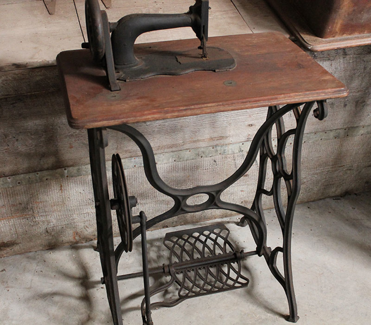 An older 1800s machine on a treadle stand.