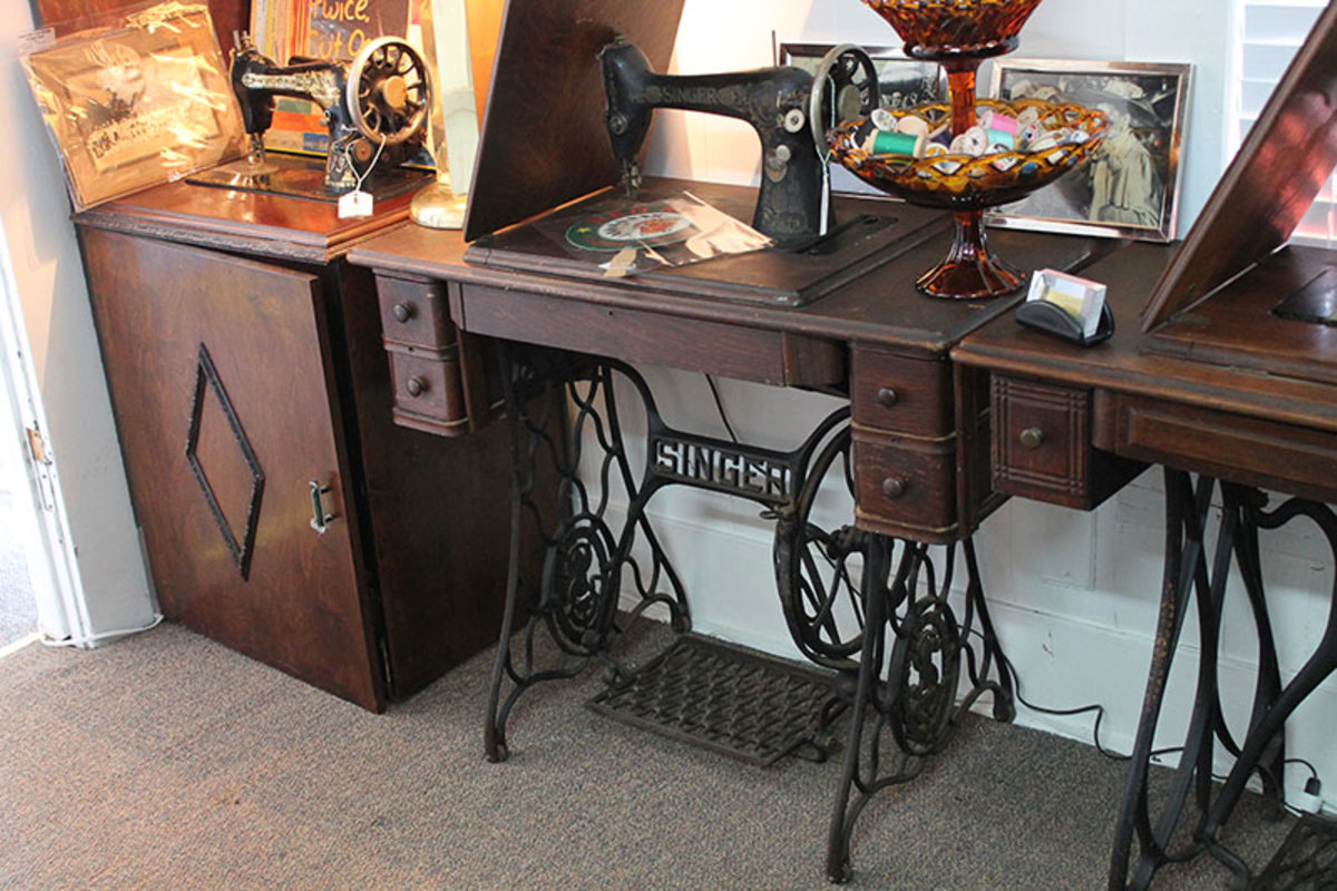 A display of treadle sewing machines note the more modern cabinet on the left.
