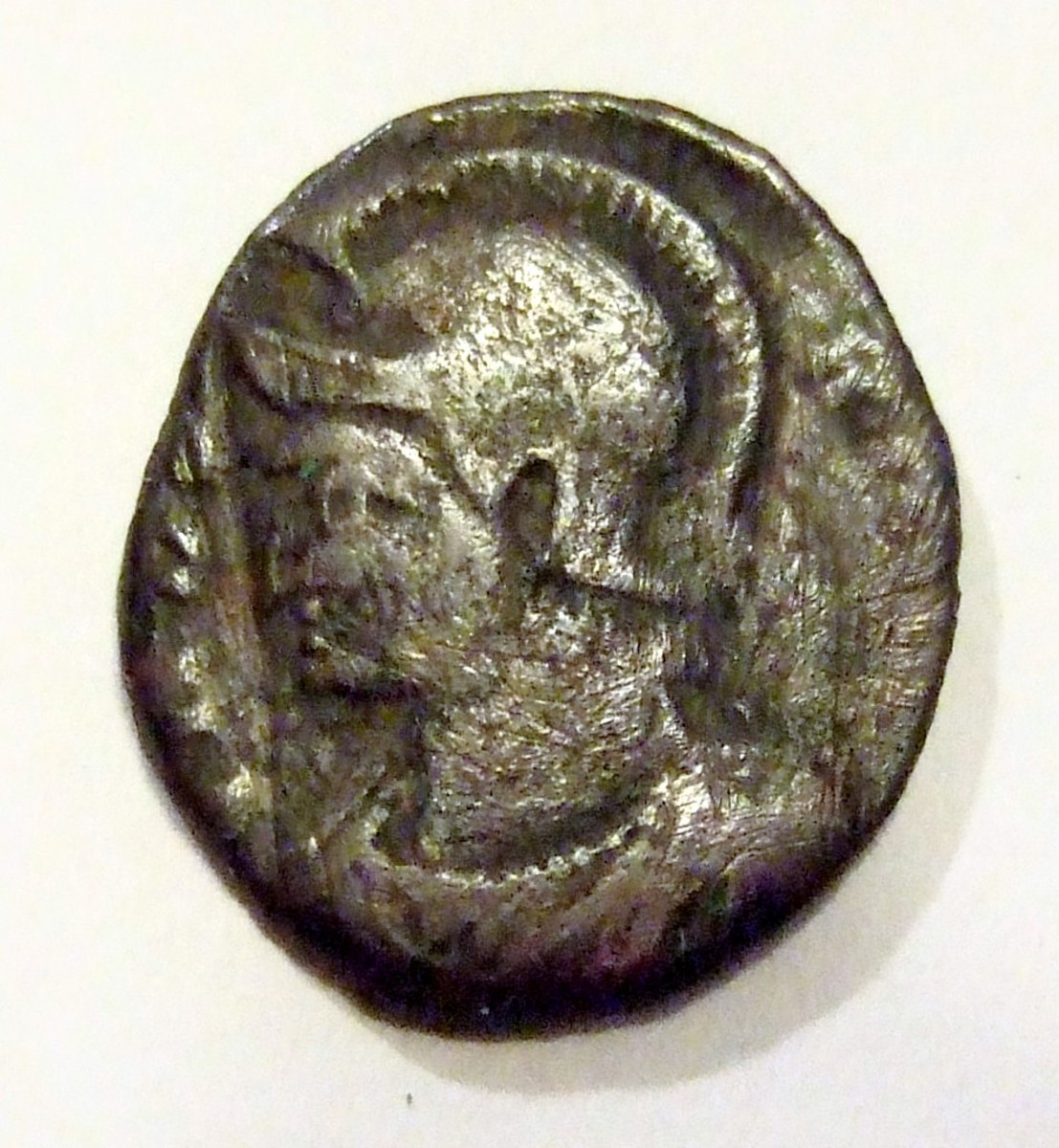 Helmeted portrait of Constantine the Great on this side of the coin, slightly larger but much thicker than a dime.