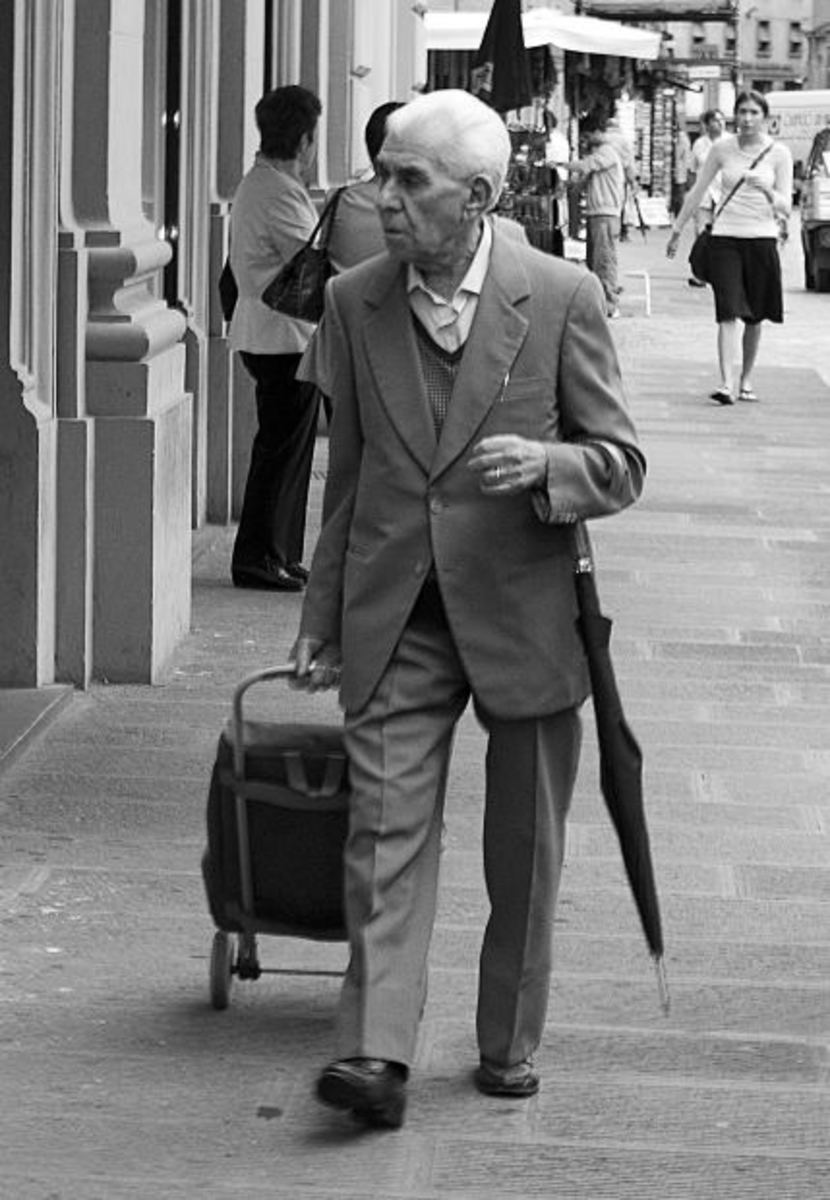 Elderly man walking with rolling suitcase and umbrella