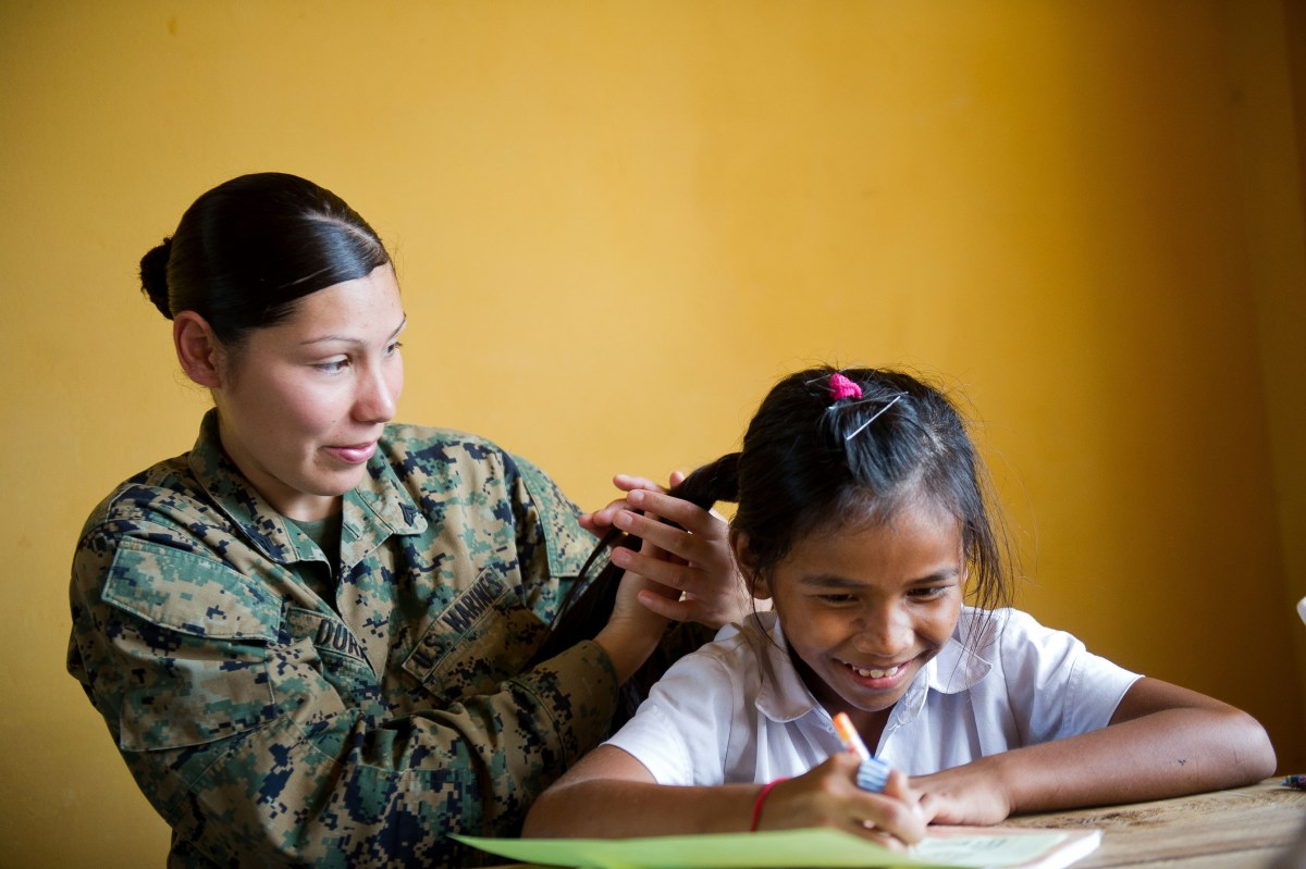 Box braiding forms a basis for bonding. Here an officer box braids a Cambodian girls hair during a community outreach.