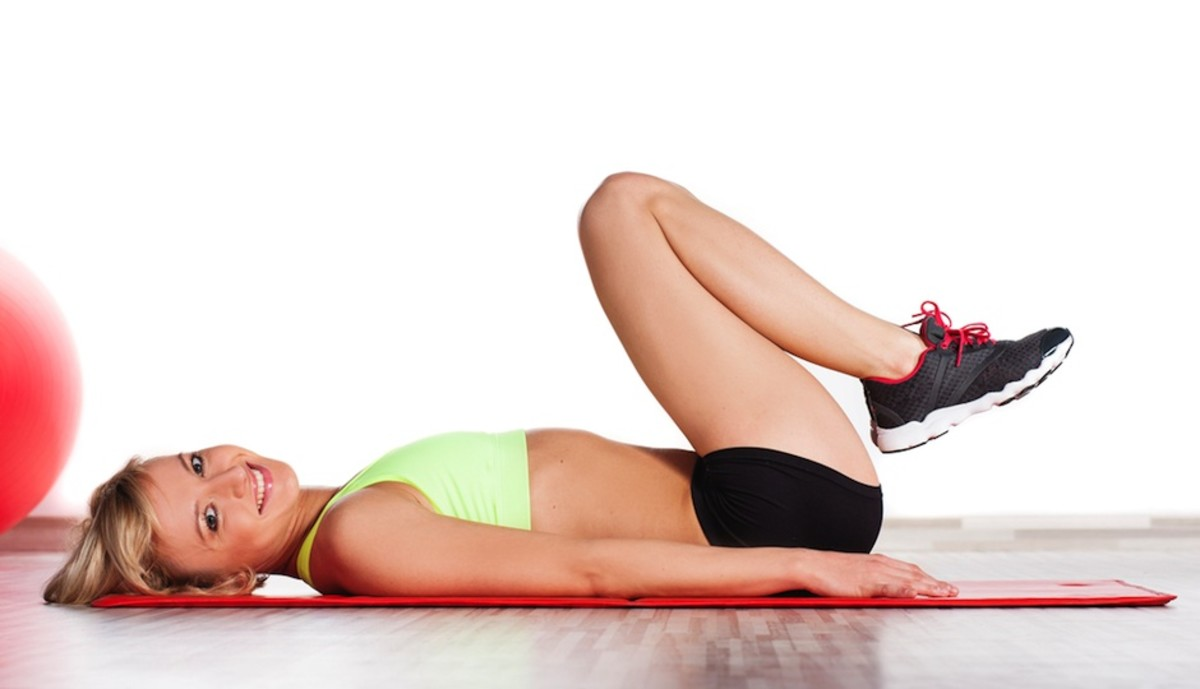 beautiful smiling blond girl in two fitness fitness outfit laying on the floor with her knees tucked