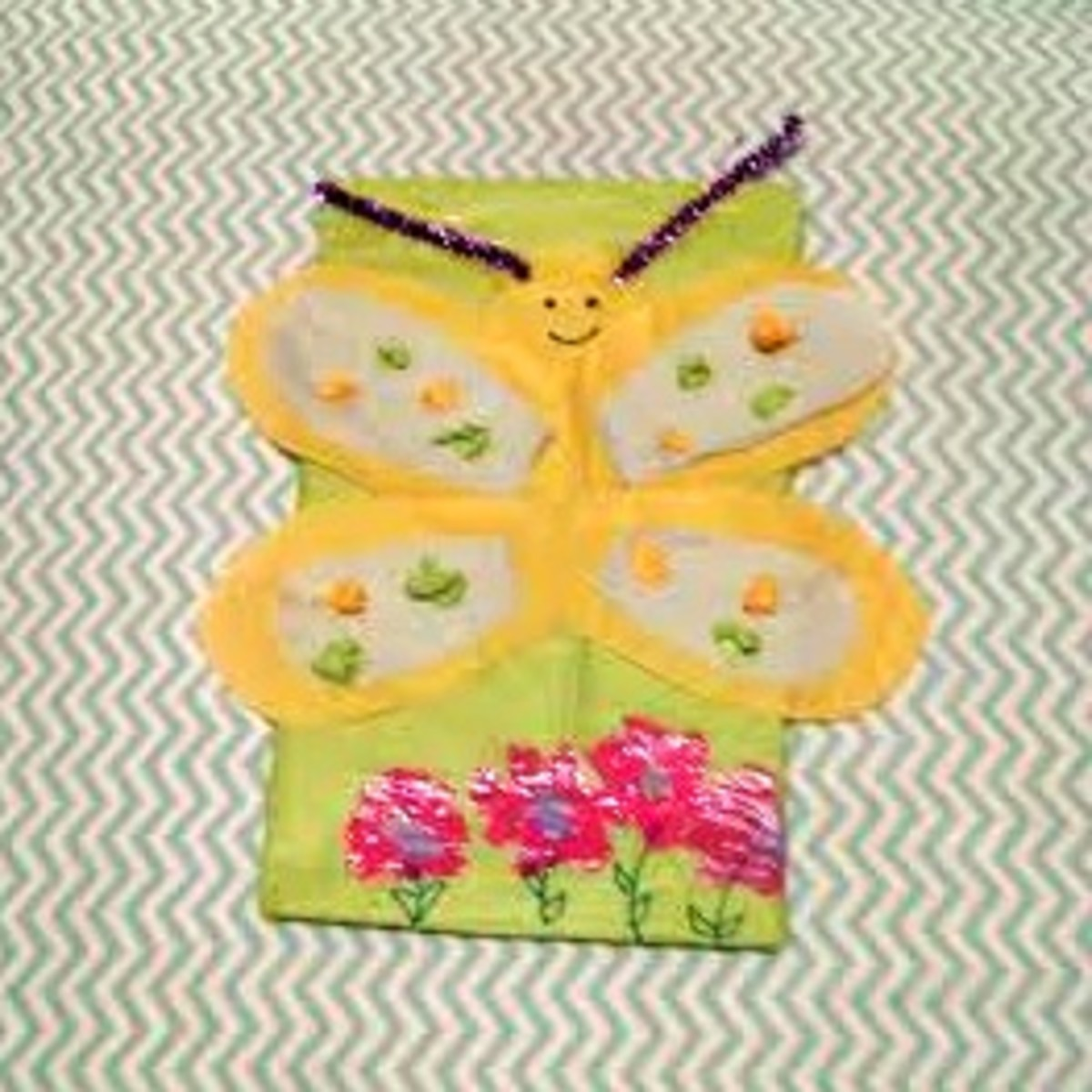 My daughter likes butterflies so I helped her make this one using the back of an oatmeal box, tissue paper and pipe cleaners for the antenna.  She wanted to paint flowers at the bottom, giving it a true Spring feeling!