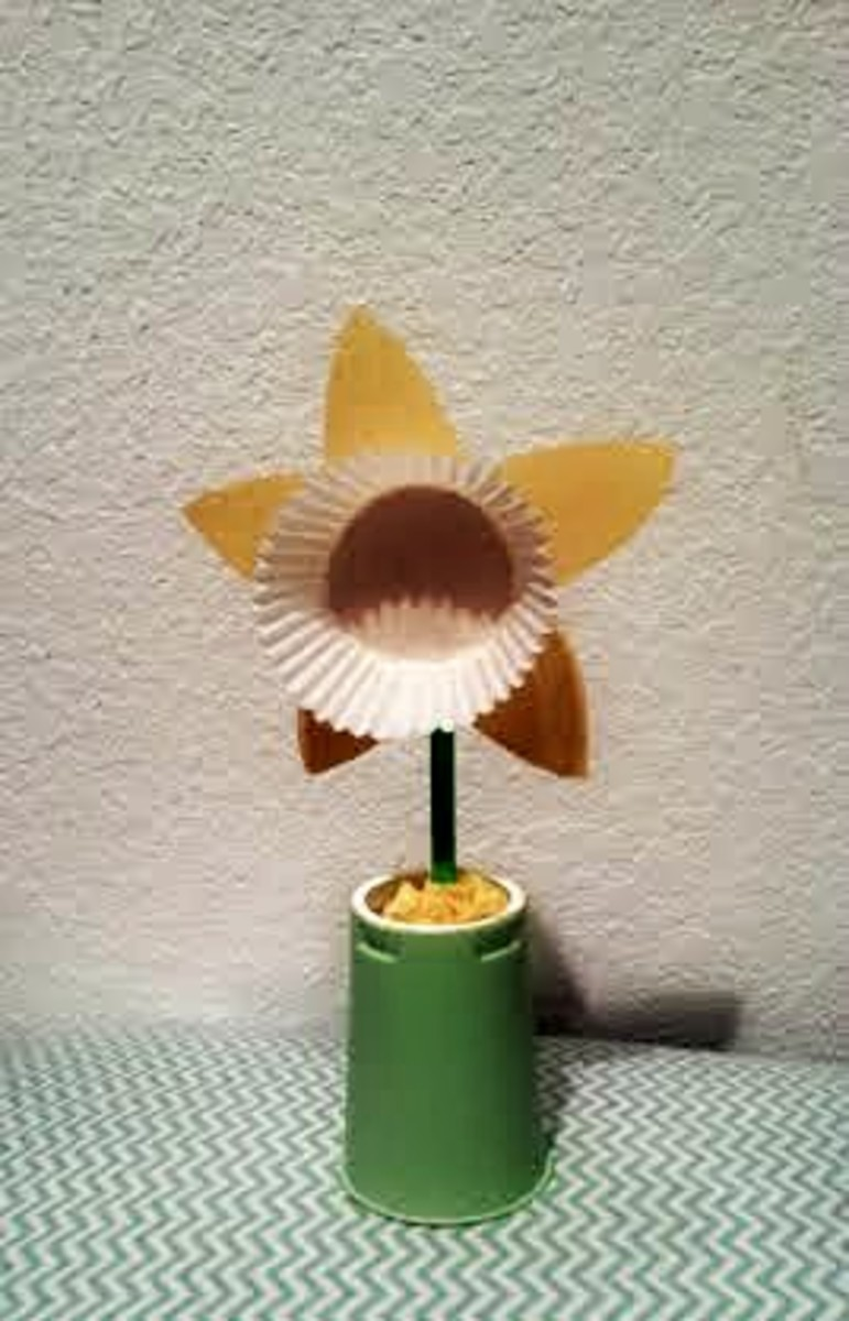 Paint yogurt cup, then place tissue paper to fill the cup.  Cut out petals with construction paper and glue white cupcake liner in the middle.  Use a green straw as the stem or a popsicle or lollipop stick. This is Another popular craft on Pinterest!