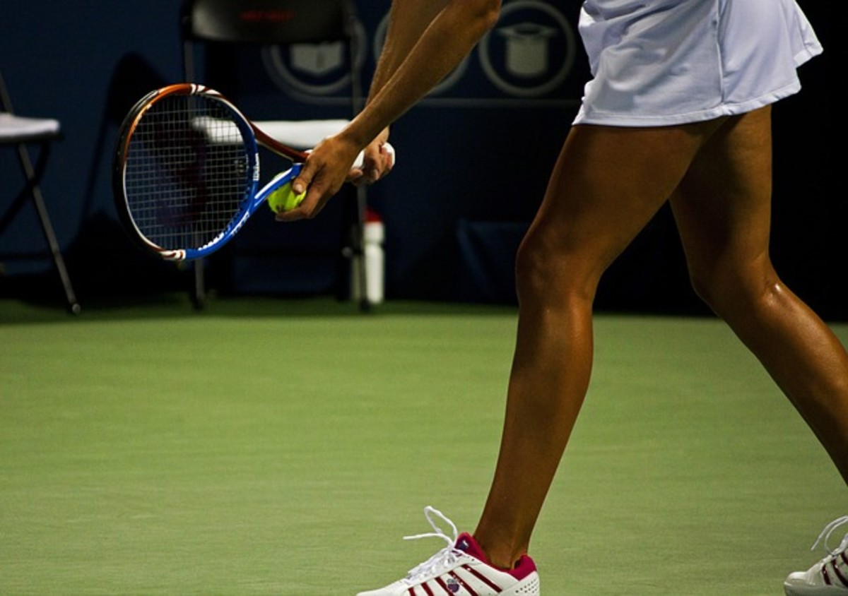 Female player lining up to serve.  Variation is usually the key to successful serving at singles. Placement, spin, and speed should all be  mixed up to keep your opponent guessing where to stand and how to respond.