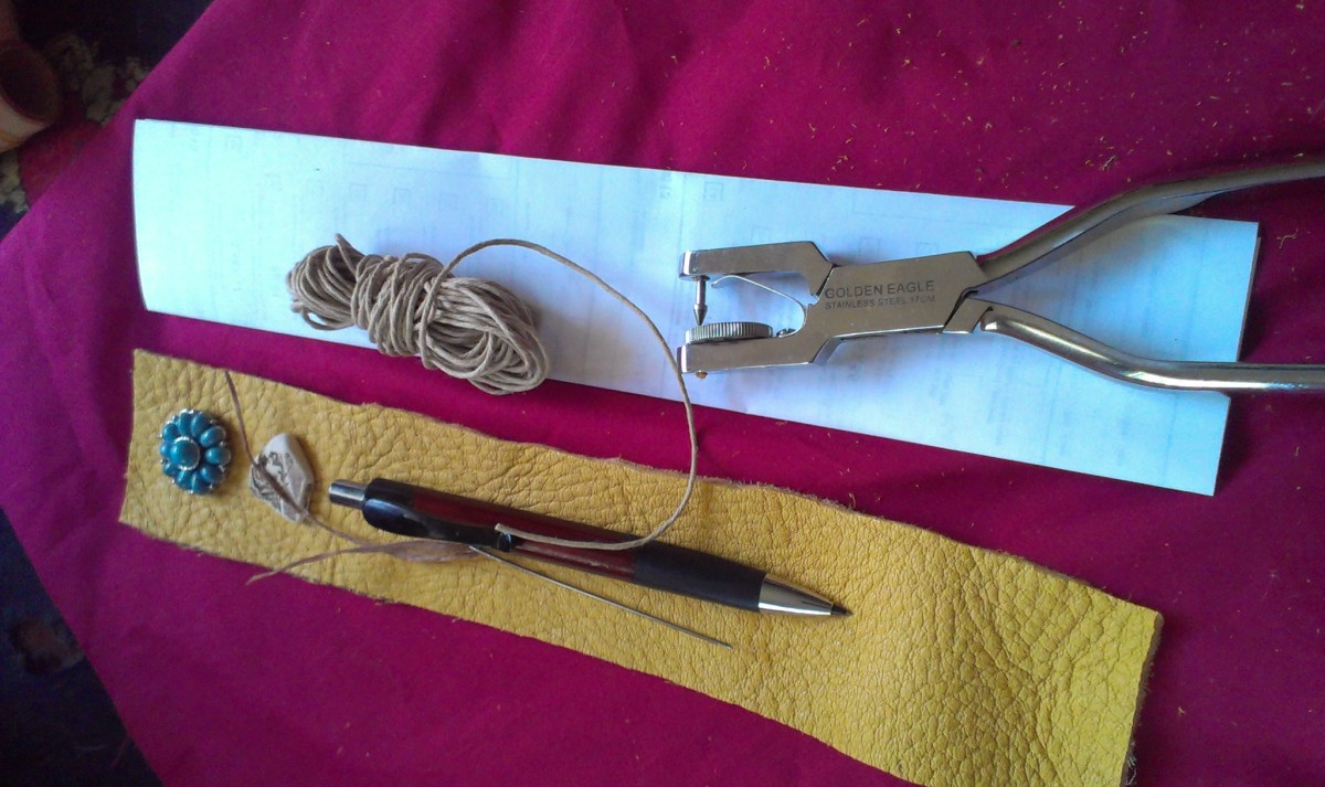 needle, thread, leather, hole punch, straight edge, beads for fastening