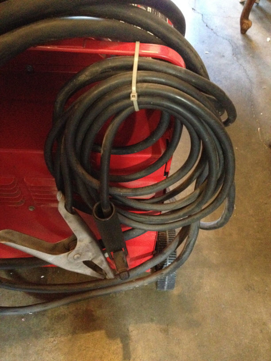 Arc welding lead rolled up and secured along with the ground clamp.