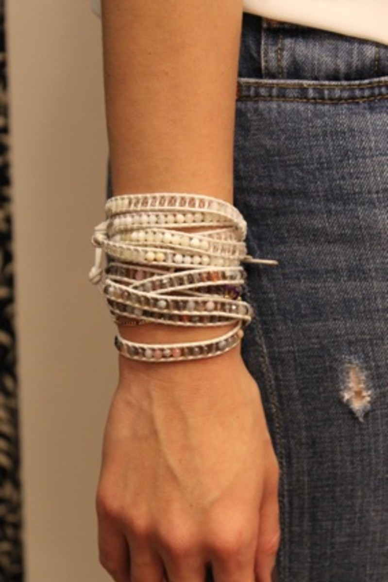 layers of bracelets on woman wearing fashionable jeans with hole