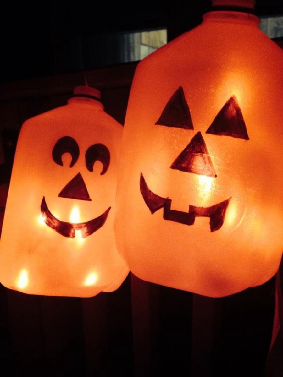 Milk Jug Pumpkins lit up with orange string lights