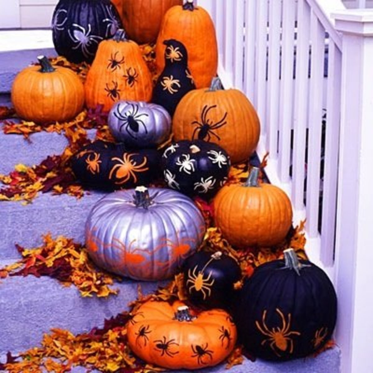 This idea using a bunch of painted and drawn on with spider stencils is just a couple of many DIY easy pumpkin decorating ideas.