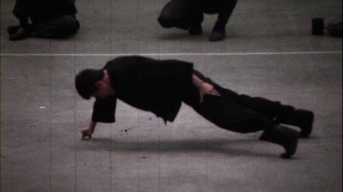 Bruce Lee performing his legendary 2 finger push up.
