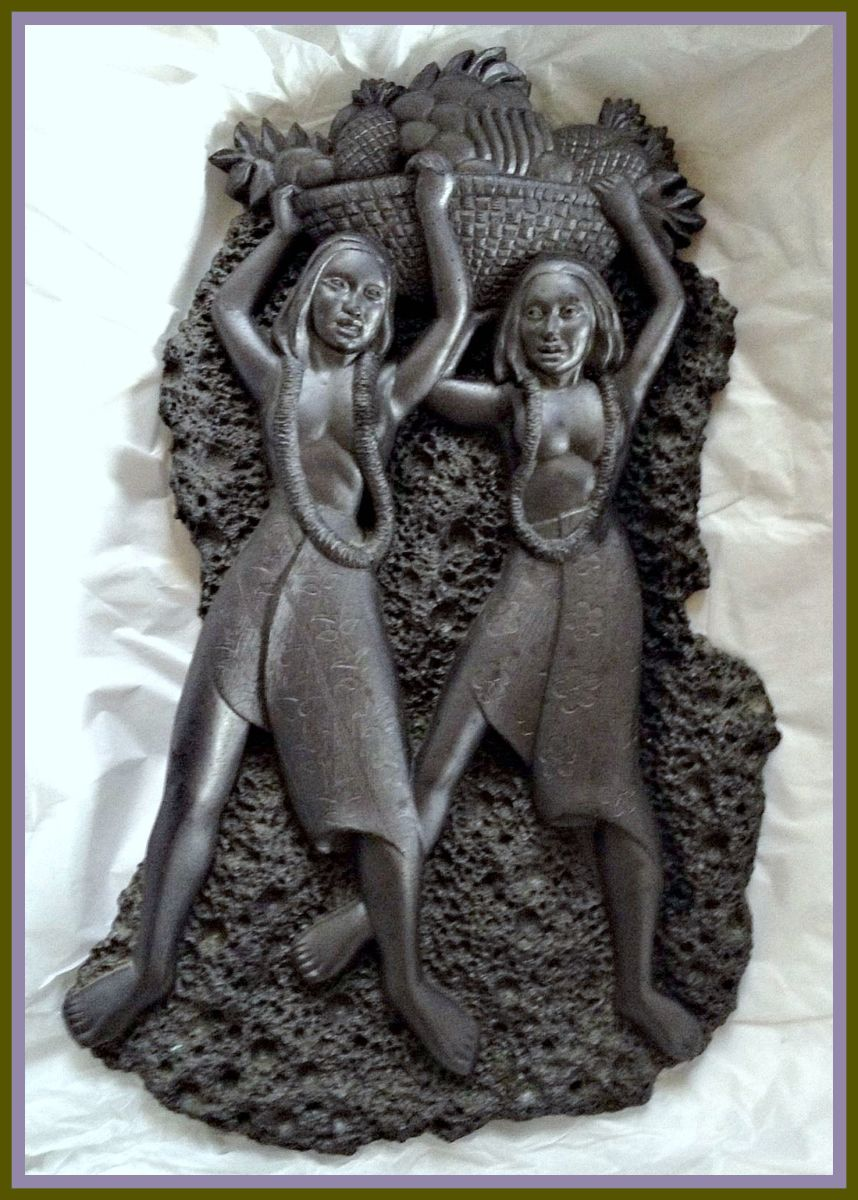 "A vintage black lava Coco Joe wall décor plaque depicting two Hawaiian Hula Girls with a bowl of pineapples above their heads. It measures approximately 12"" long and 7"" at its widest.  It weighs 2 lbs 5.0 oz. Makes a great addition to your tiki bar."