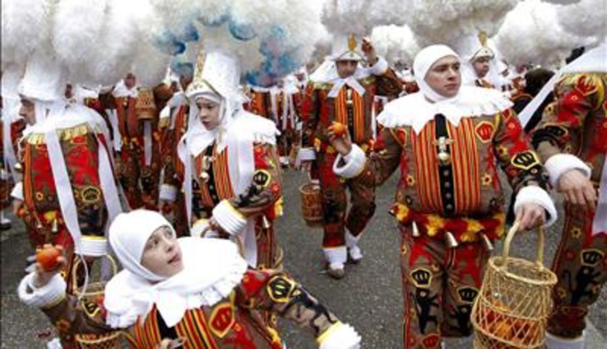 Masks off, it's time to start throwing oranges. Binche Mardi Gras Carnival, Belgium.