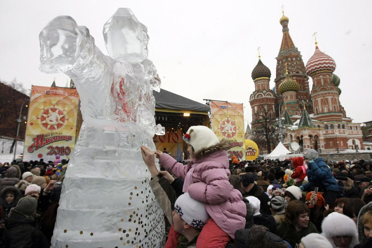 People stick coins to an ice sculpture of Lady Maslenitsa.