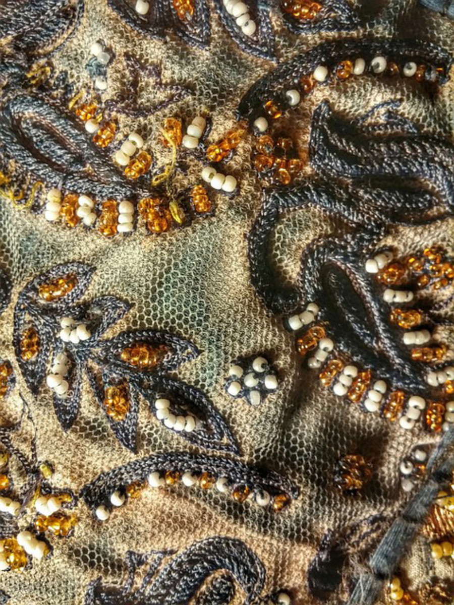 A sample of beads threaded into the established design of the cloth.