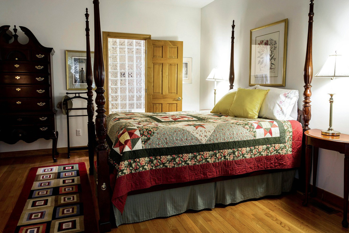 A bed quilt on a 4-poster bed adds to the decor of the bedroom.
