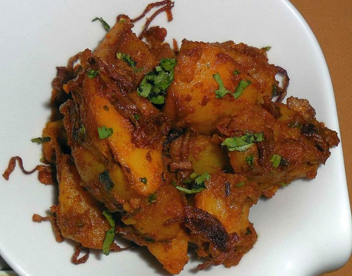 Aloo Dum preparaed with cut potatoes and garnished with coriander leaves