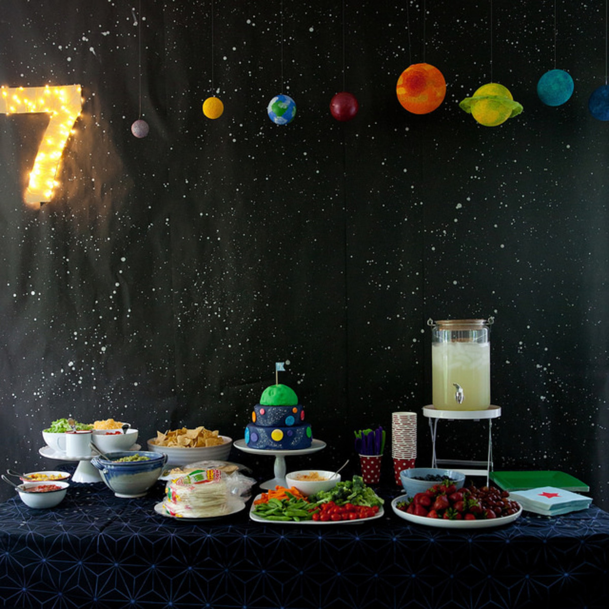 Outer space party table with night sky and planet backdrop and a delicious array of Space theme party food.