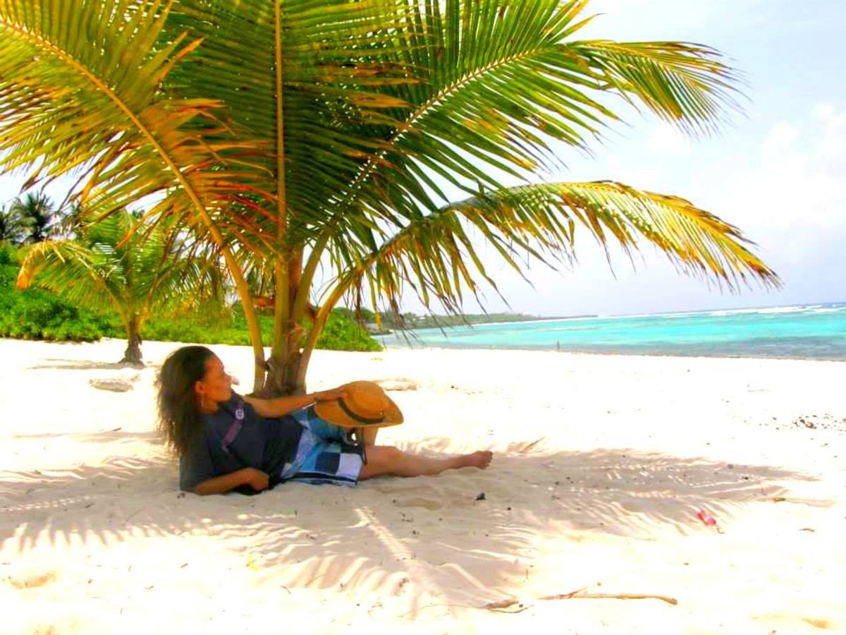 The author relaxing under a coconut palm at one of her favorite hangouts, Spotts cemetery beach