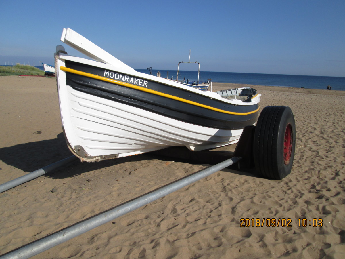 Not far south, a coble has been drawn up on its trailer onto the sands below Marske village