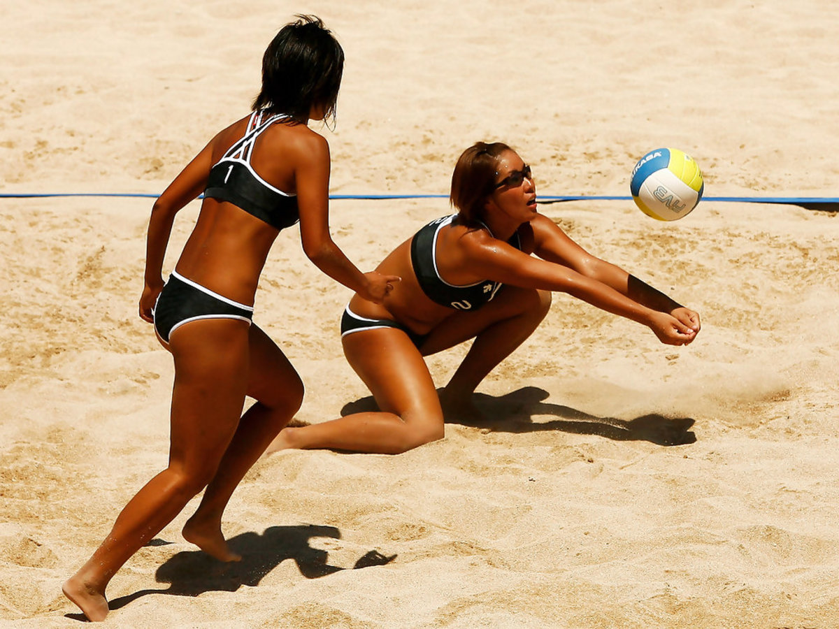 Ayumi Kusano (right) hits the ball as her partner Mutsumi Ozaki looks on.