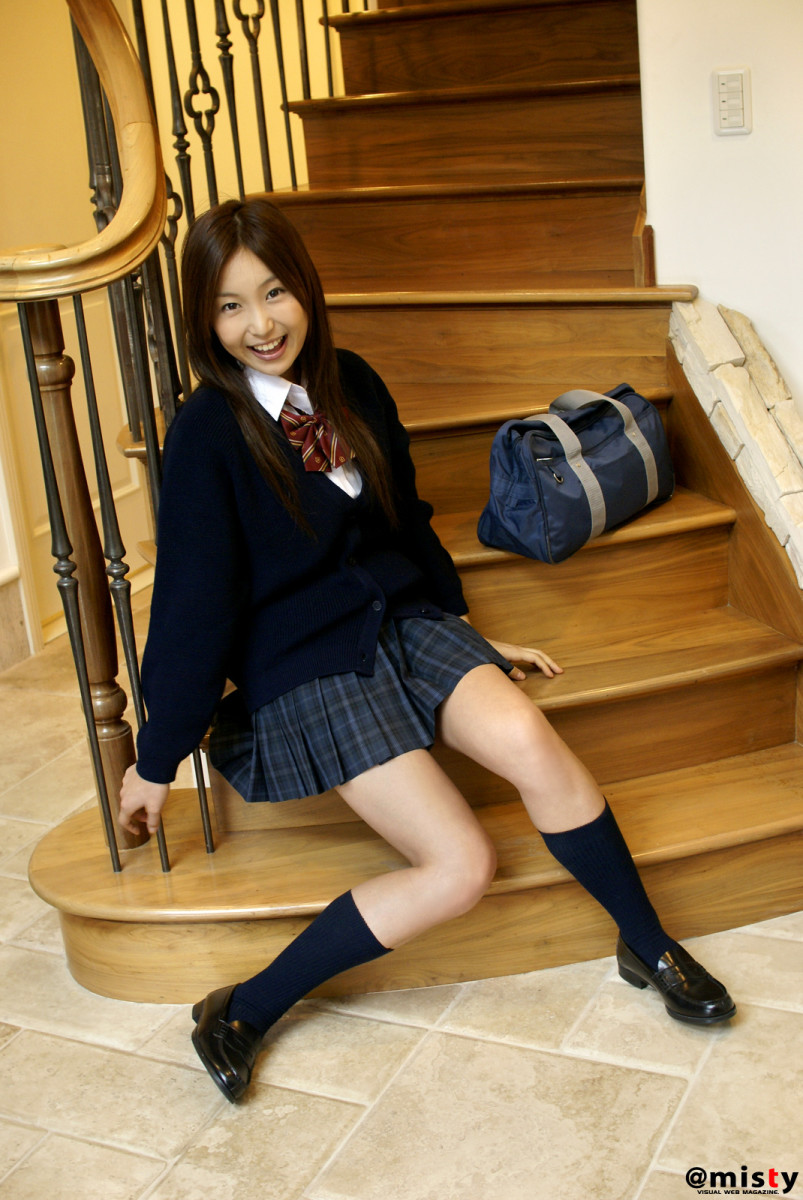 Saori Yamamoto in this photo is sitting down at the bottom of a long staircase and she is dressed in a traditional Japanese school girl uniform.